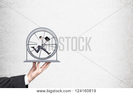 Hand holding spinning wheel with businessman running inside. Concrete background. Concept of hard work.
