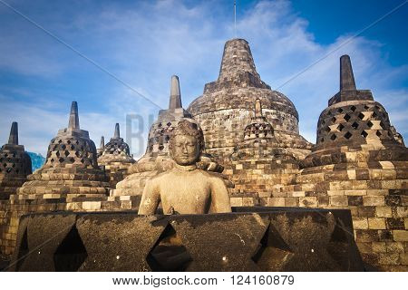 Buddha statue at Borobudur temple at sunset in Yogyakarta, Java, Indonesia.