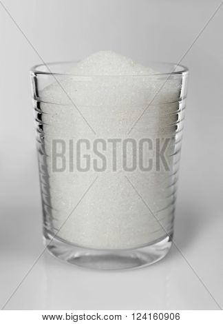 Old fashioned glass filled with granulated sugar on grey background