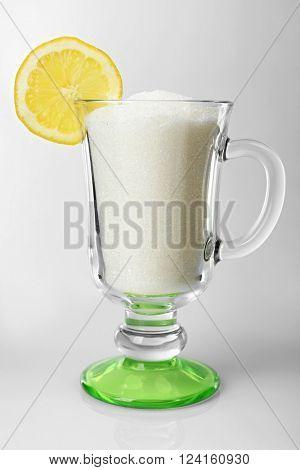Irish coffee glass with granulated sugar and slice of lemon on grey background