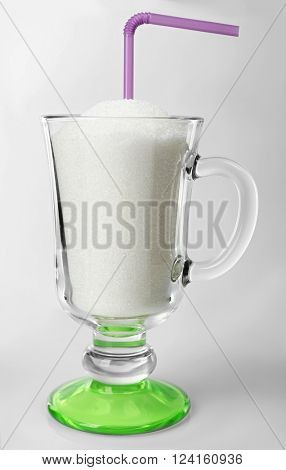 Irish coffee glass with granulated sugar and cocktail straw on grey background