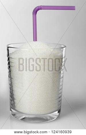 Old fashioned glass with granulated sugar and cocktail straw on grey background
