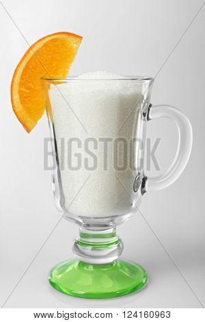 Irish coffee glass with granulated sugar and slice of orange on grey background