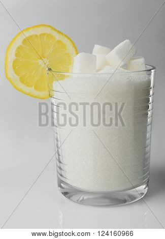 Old fashioned glass with lump, granulated sugar and slice of lemon on grey background