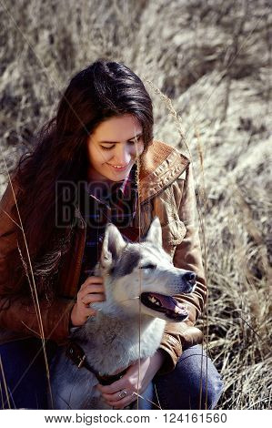 Girl husky is scratching behind the ear and smiles . Spring field.