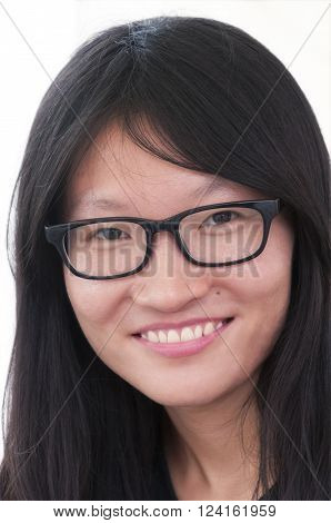 A chinese woman against a white background wearing black rimmed glasses smiling.