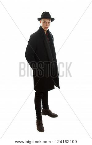 young serious man dressed in coat standing white background