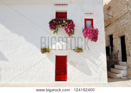 characteristic white and red colored house with flowers at the window in Monopoli near Bari Apulia Italy