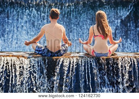 Happy family on honeymoon holidays - just married couple in yoga lotus position after swimming in waterfall pool. Active lifestyle people outdoor travel activity on summer vacation on tropical Bali.