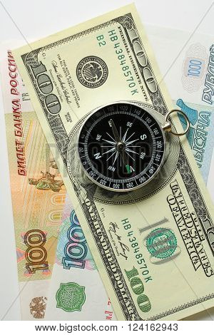 Compass on the background of banknotes rubles and dollars