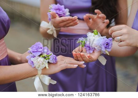 bridesmaid in purple dresses. Close up of bridesmaids hands with colorfull bouquet.