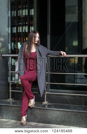 Chic Brunette Woman In Marsala Overall Standing  Outdoors
