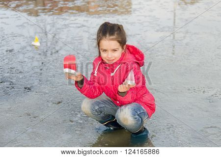 Happy cute little girl in rain boots playing with handmade colorful ships in the spring creek standing in water. Kids play outdoors