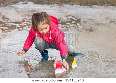 Cute little girl in rain boots playing with colorful ships in the spring creek standing in water. Kids play outdoors