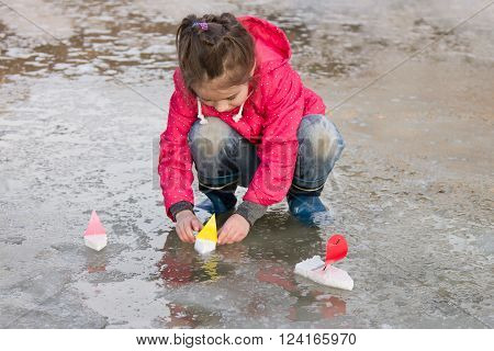Cute little girl in rain boots playing with ships in the spring water puddle. Kids play outdoors