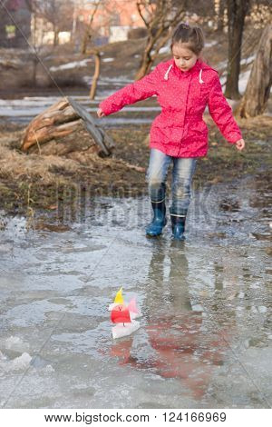 Cute little girl in rain boots playing with colorful ships in the spring creek walking in water. Kids play outdoors