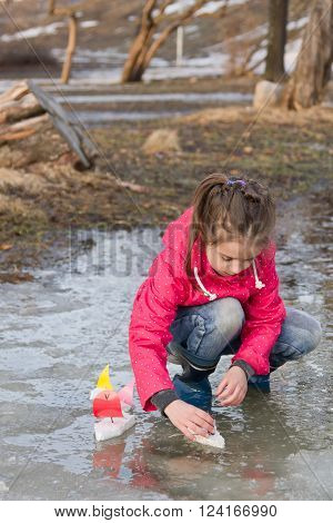 Beauty little girl in rain boots playing with handmade ships in the spring water puddle. Kids play outdoors