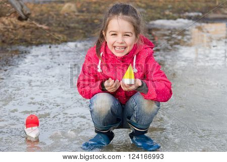 Happy cute little girl in rain boots playing with ships in the spring creek standing in water. Kids play outdoors