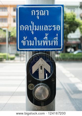 push button for Red traffic light in Thailand. thai language -- (Selective focus)