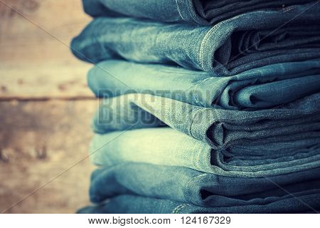 Stacked fashion jeans closeup. Retro toned photo.