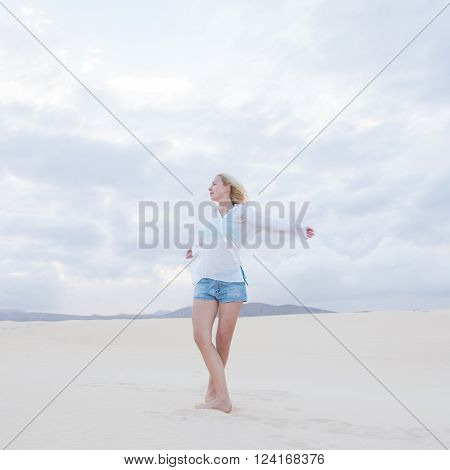 Relaxed woman enjoying freedom feeling happy at beach in the morning. Serene relaxing woman in pure happiness and elated enjoyment with arms outstretched. Copy space.