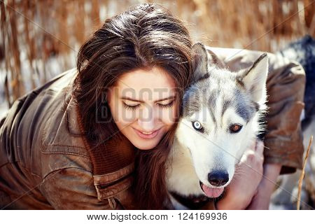 Beautiful woman with husky outdoors.Happy brunette woman with smiling siberian husky dog, sitting in a poppy field on a sunny day, on a walk with dog