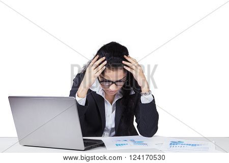 Picture of Indian business woman holds her head and looks stressful with financial graph and laptop on the table