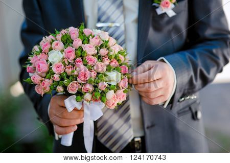 groom is holding a wedding bouquet in wedding day
