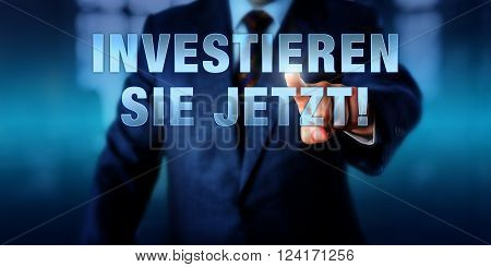 Businessman is pressing INVESTIEREN SIE JETZT! on a touch display interface. German language call to action meaning DO INVEST NOW. Virtual text on a transparent visual screen. Financial concept.