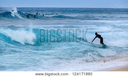 Pipeline Beach, Hawaii - April 26, 2015: Surfer on a wave with other surfers in the background in the sea