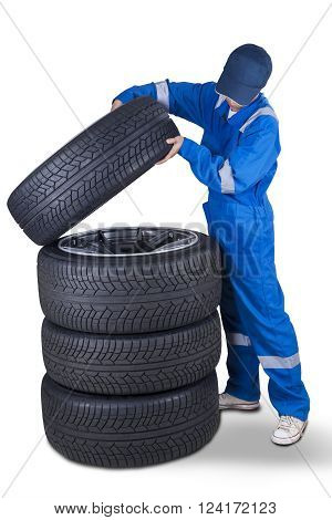 Image of a car mechanic wearing uniform and puts a tire into a stack of tires isolated on white background