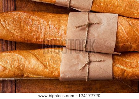 Freshly baked French baguettes on dark wooden table, close-up