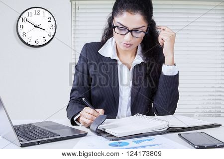 Picture of female entrepreneur wearing formal suit and glasses in the office while working and writes a note