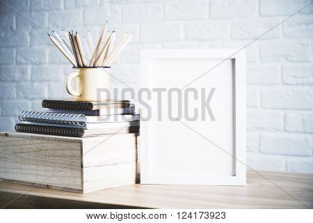 Desk with blank picture frame and pencils in iron mug placed on book and wooden box. Mock up