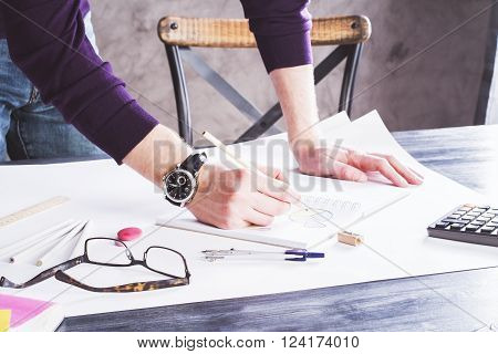 Sideview of businessman drawing business charts in copybook on table with office tools