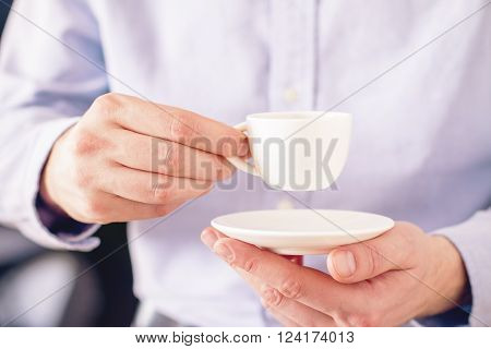Male in purple shirt holding blank white coffee cup and saucer