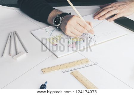 Man drawing business charts in copybook on white surface with office tools