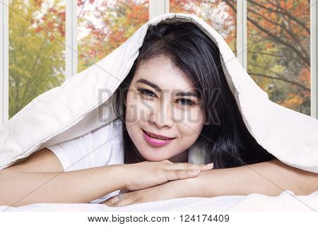 Pretty young woman smiling at the camera while lying on the bed under duvet shot with autumn background on the window