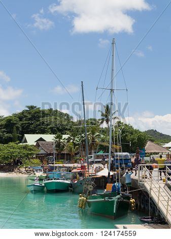 La Digue - November 10 2014: Boats and yachts stand at the port of the island of La Digue and people working in the port on a sunny day November 10 2014 the island of La Digue Seychelles