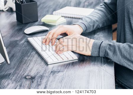 Sideview of desktop with male hands typing on keyboard computer screen and office tools