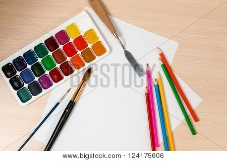 paints and pencils for drawing are around a blank slate