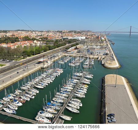 Lisbon, Portugal - March 03, 2016:  Belem marina with yachts and the river Tejo and the Ponte 25 de Abril  Lisbon Portugal.