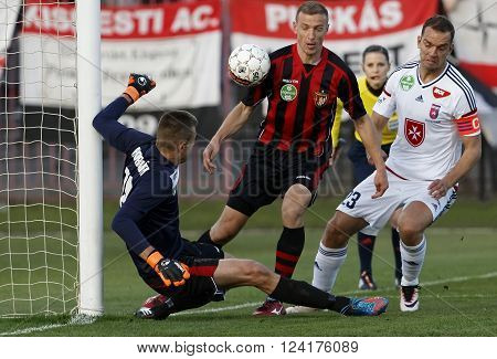 BUDAPEST HUNGARY - APRIL 2 2016: Goalkeeper Andras Horvath (l) and Djordje Kamber of Honved cover the ball from Roland Juhasz (r) of Videoton during Budapest Honved - Videoton OTP Bank League football match at Bozsik Stadium.