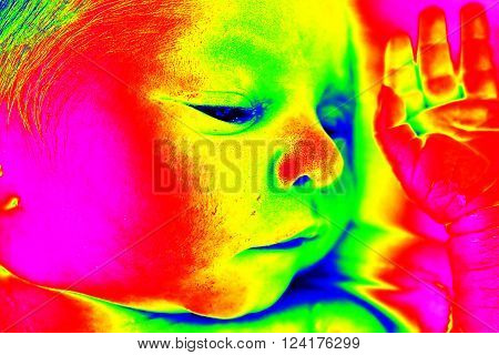 Infrared thermovision image of newborn baby girl face and head resting in a hospital bed. Analysis of the surface skin body temperature
