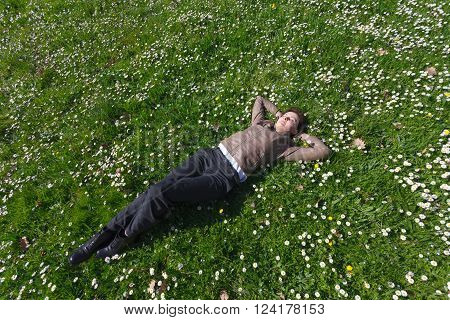Relaxing young woman in pants and leather jacket lying on grass and spring flowers