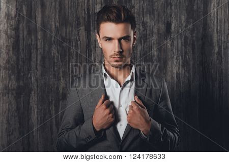 Portrait Of  Stylish Businessman Touching Jacket On Gray Background