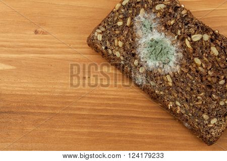 Moldy bread in wooden table. Unhealthy food. Spoiled food.
