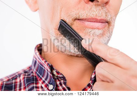 Close up portrait of handsome aged man combing his beard
