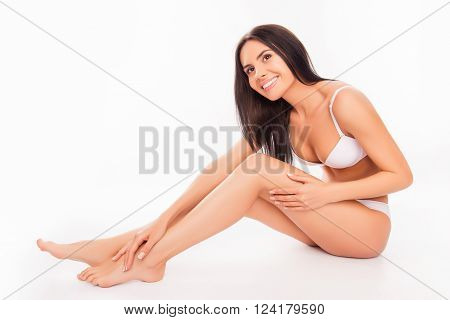 Cute Pretty Young Woman Sitting In White Underwear And  Touching Her Legs