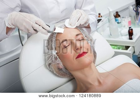 Professional beautician is making cavitation peeling for mature woman. She is cleaning female forehead with a sponge. Her patient is lying and relaxing
